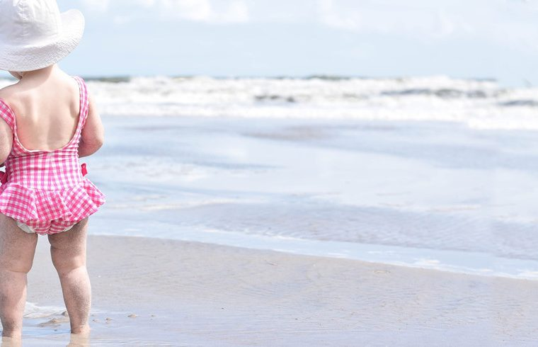 Niña en la playa con pañal bañador para bebé